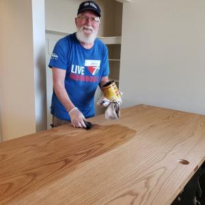 PHOTO: FUMC volunteer stains door at H4H renovation