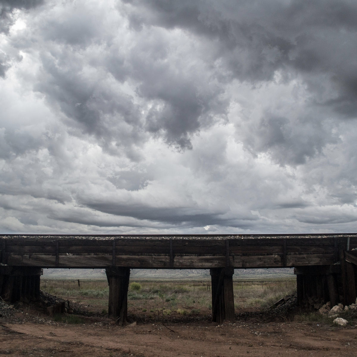 Gray clouds and a railroad bridge in the desert
