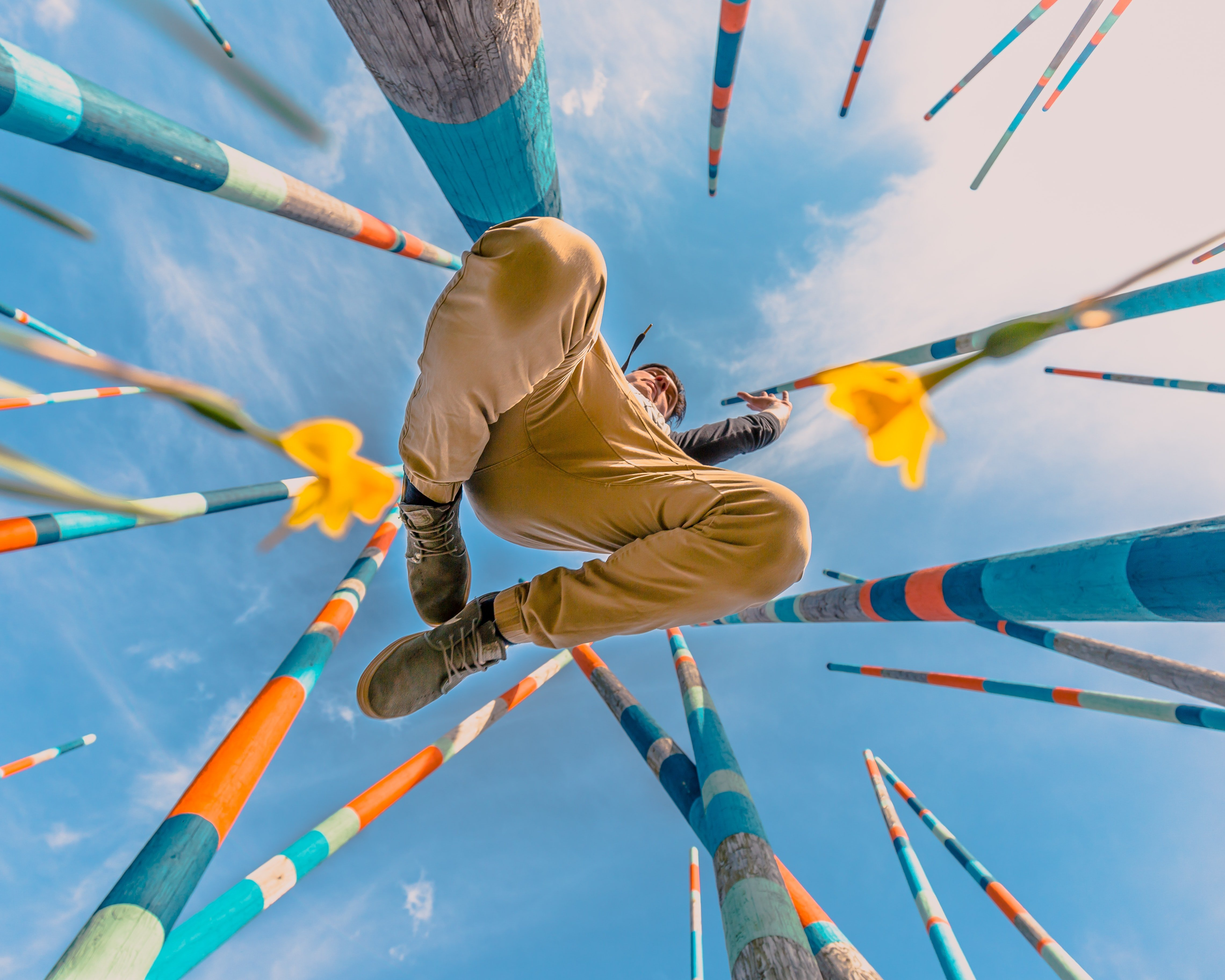 Young man jumping high in the air, with colourful sticks surrounding him