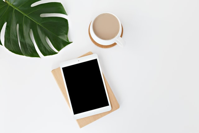 phone and coffee cup with a plant leaf on a desk