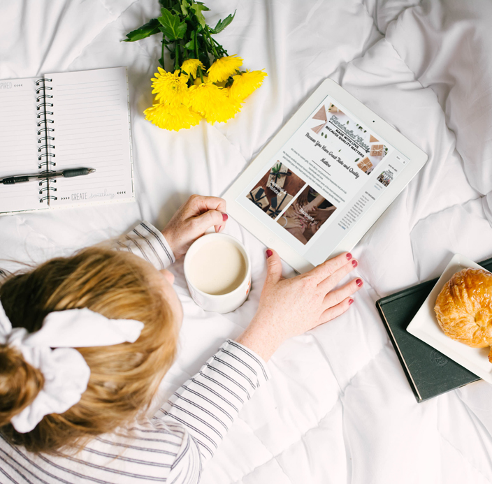 Subscribe to handcraftedshops newsletter, woman on bed with iPad and coffee looking at handcraftedshops website