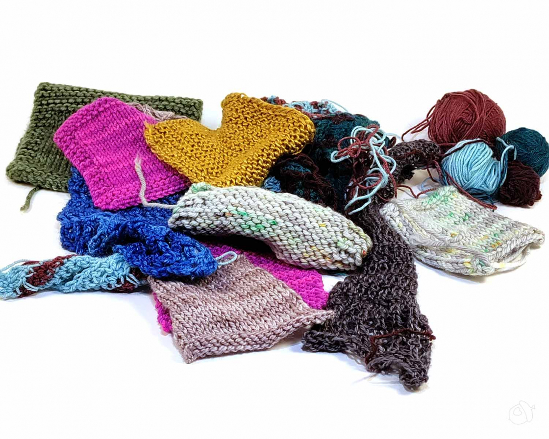 A messy pile of knit and crochet swatches in various colors and fibers on a white surface. There are some small balls of yarn still attached.