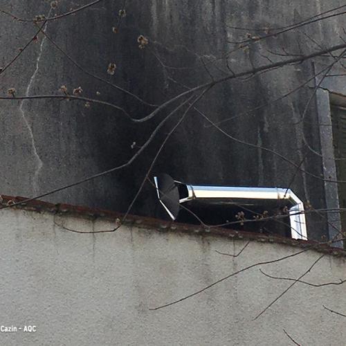 Désordre bâtiment : Le conduit de cheminée est plié avec un coude et positionné au milieu d'un mur près d'une fenêtre. Concours Photo AQC 2021