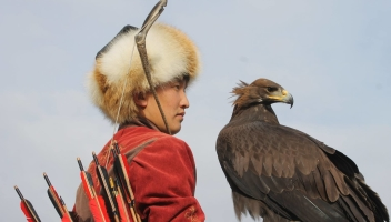 Enable images to see a photo of a Kyrgyz archer on horseback holding an eagle