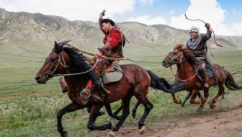 Enable images to see a photo of two Kyrgyz archers on horseback