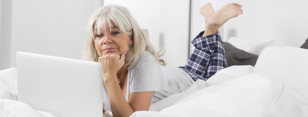 Older woman reading on her laptop while lying in bed