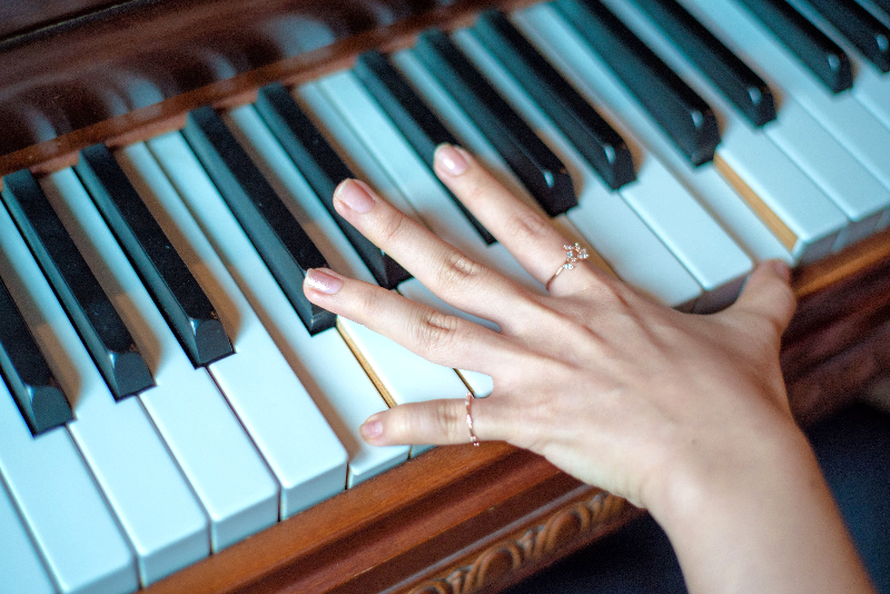 Get straight into learning piano today with 'Super Basics'. *Young woman's hand on the piano keys outstretched.*