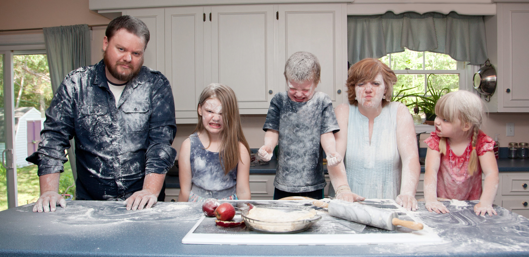 family baking food in a messy kitchen
